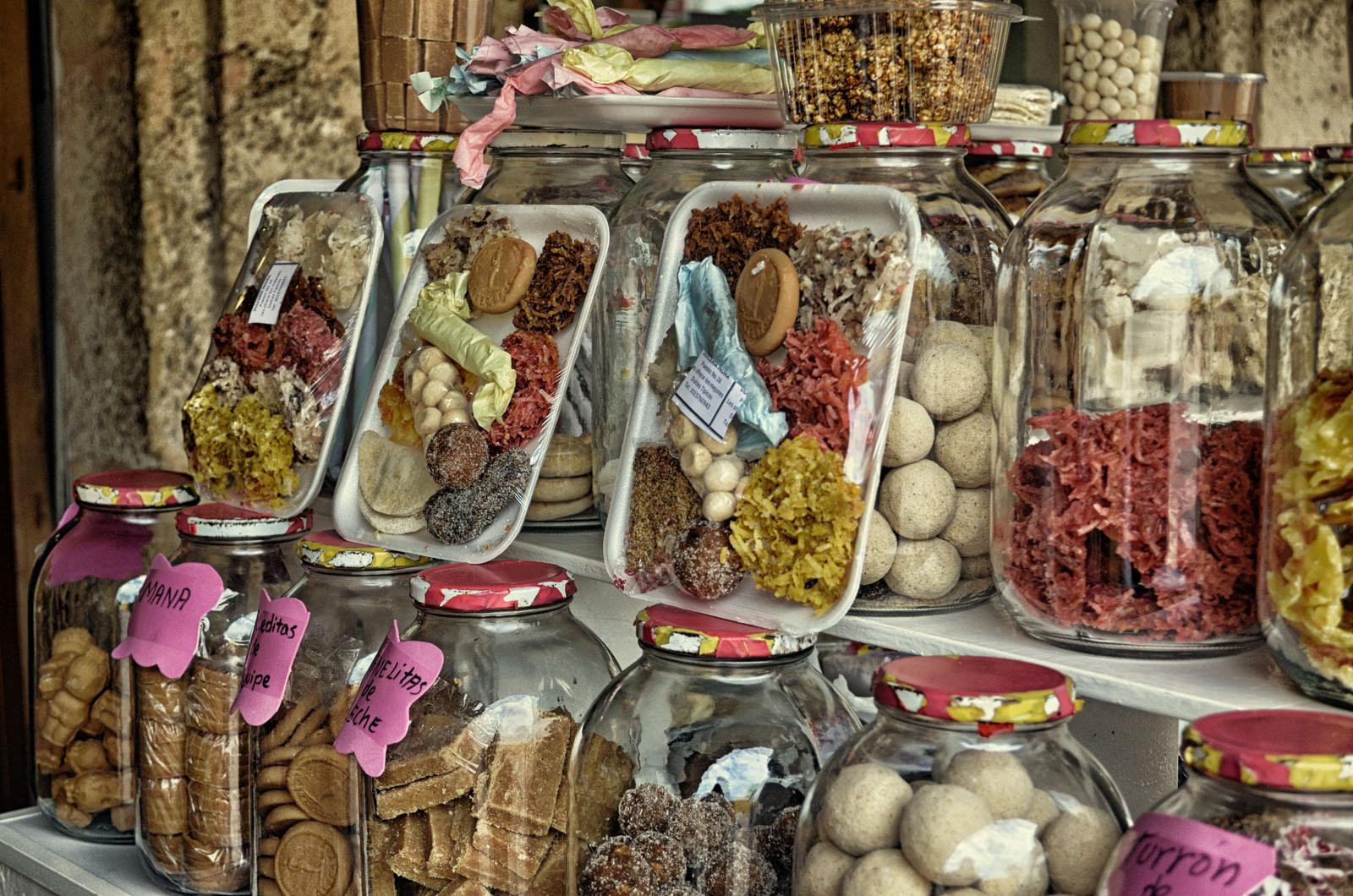 Doces coloridos e atraentes são expostos nas bancas do famoso Portal de Los Dulces.
