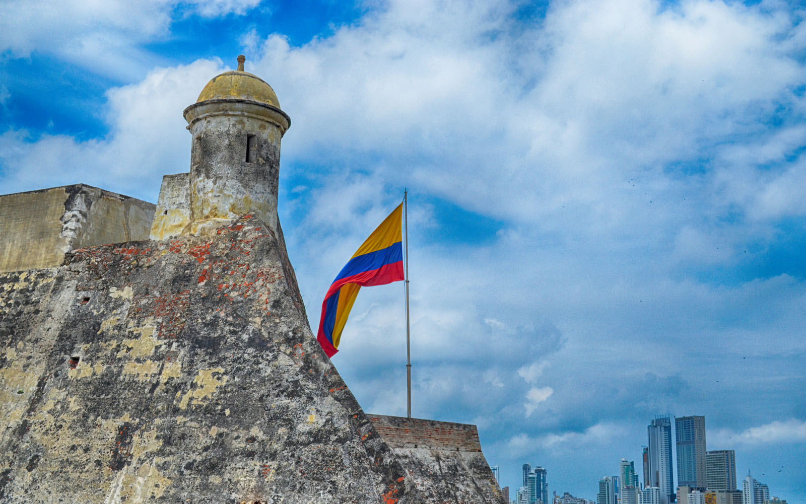 Torre do Castillo de San Felipe de Barajas ao lado da bandeira, contrastando com edifícios modernos ao fundo.