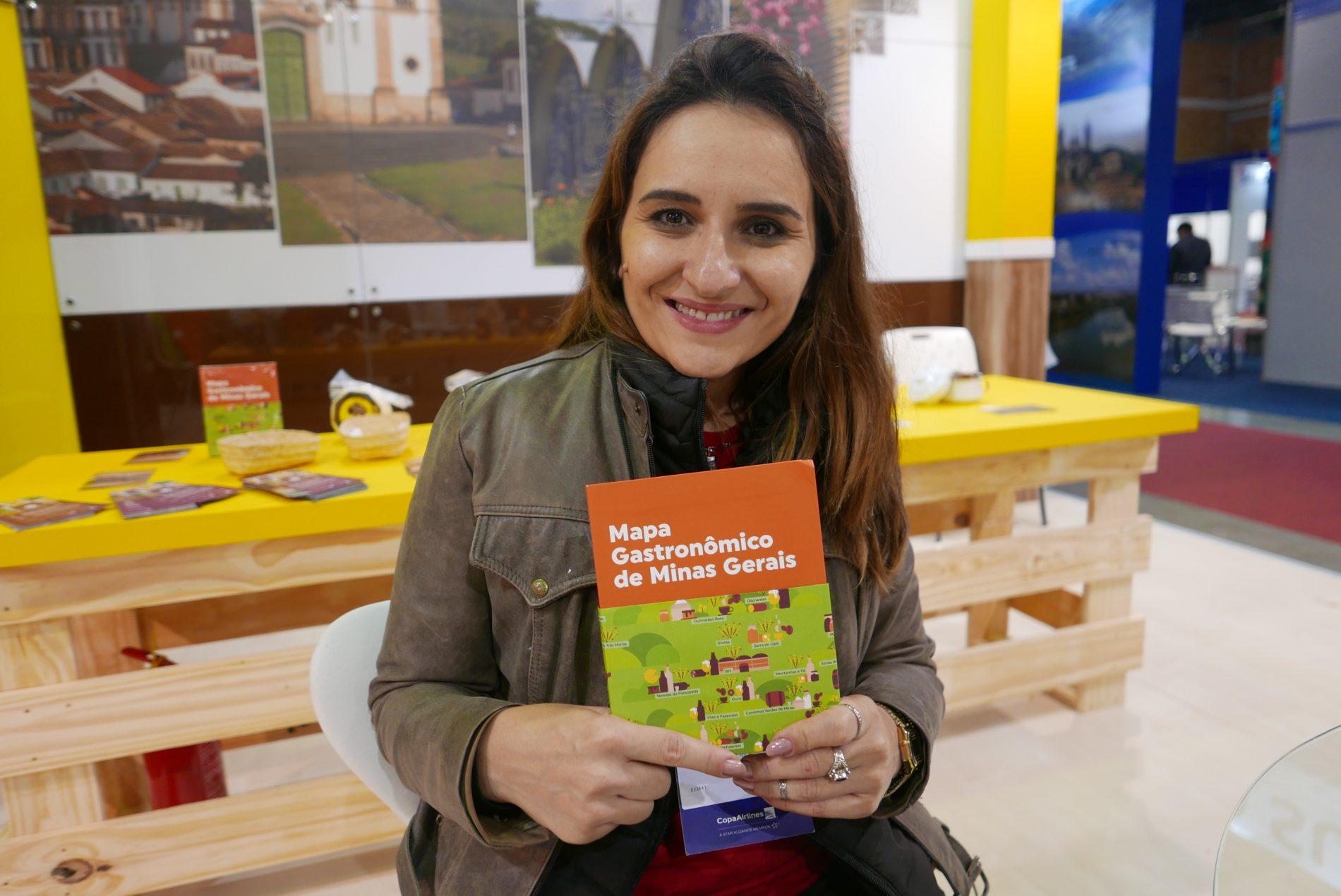 Nathalia Laranjo, da secretaria de Turismo de Minas Gerais e a publicação que foi destaque no Festuris: o Mapa Gastronômico de Minas Gerais