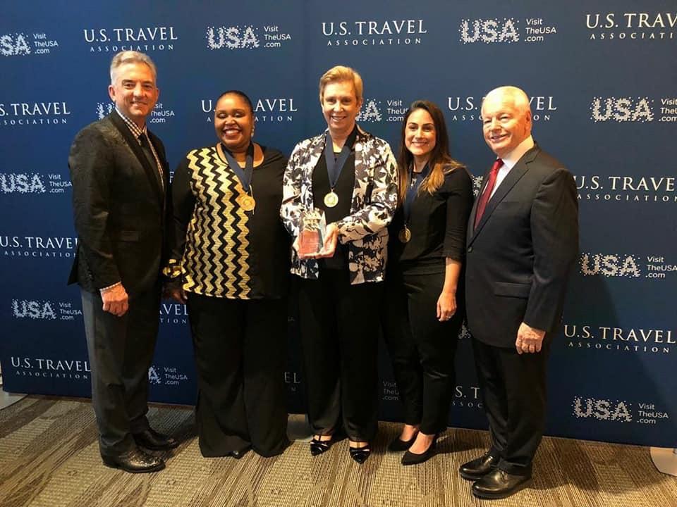 Barbara Picolo segura o troféu Chairman's Circle Honors, ao lado de Georgia Mariano e Luiza Leopoldo: o time da Flytour Viagens MMT recebeu a homenagem das mãos de Chris Thompson, presidente e CEO da Brand USA, e Roger Dow, presidente e CEO da US Travel Association