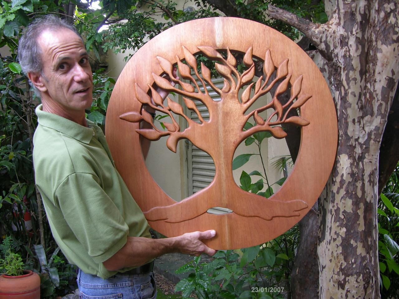 O artista plástico Sergio Monteiro de Castro e uma de suas obras em madeira: a Árvore da Vida