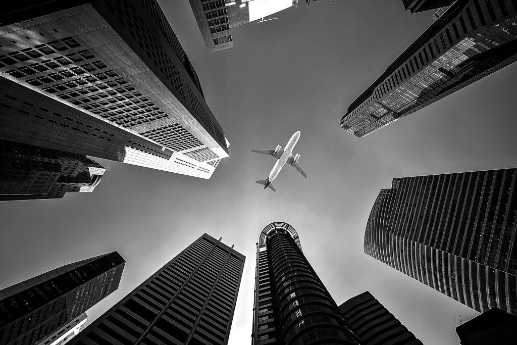 Avião entre prédios preto e branco